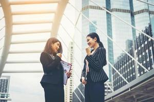 Two businesswomen stand and discuss work in front of the office