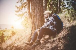 Young man traveling with a backpack in nature