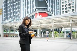 mujer de negocios, utilizar, teléfono, con, café, ambulante, en la calle