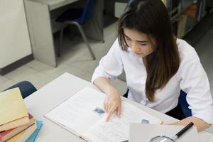 joven estudiante asiático leyendo en la biblioteca foto