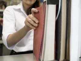 Young students finding books in university library photo