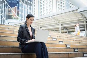 Business woman using laptop sits on the steps. Business people concept.