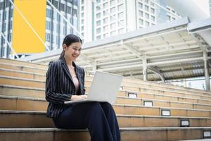 Business woman using laptop sitting on steps