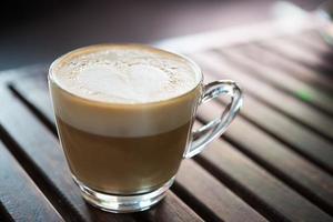 Close-up de taza de capuchino con patrón de leche en forma de corazón en el cafe foto