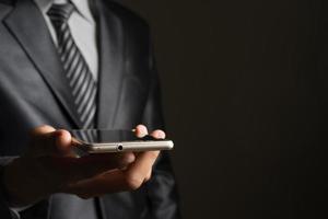 retrato, de, un, hombre de negocios, tenencia, smartphone, contra, fondo negro