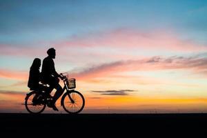 silueta, de, un, pareja joven, en una bicicleta, durante, ocaso