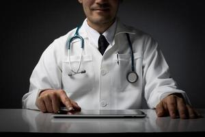 Male medical doctor with a tablet computer sitting isolated at desk