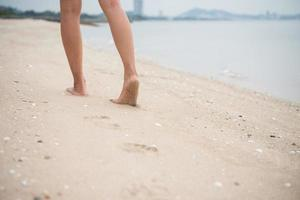 Young woman walking on sand beach leaving footprints in the sand photo