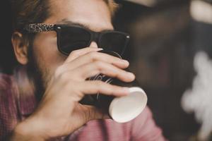 joven sentado en un café y tomando un café foto