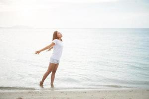 Young beautiful woman stretches her arms in the air on the beach with bare feet