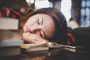 Portrait of a hipster teenage sleeping on table at cafe