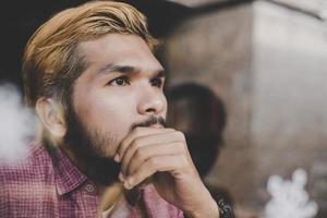 Young hipster man sitting in coffee shop thinking and looking away photo
