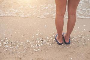 Young woman with flip flop sandals on the beach photo