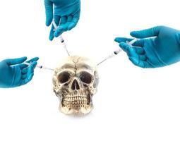 Hands wearing medical gloves injecting syringe into skull photo