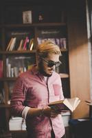 Young bearded hipster reading a book in a cafe photo