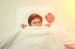 Young woman lying on the bed looking at the alarm clock in the morning