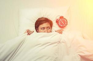 Mujer joven acostada en la cama mirando el despertador por la mañana
