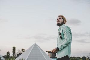 hombre joven inconformista de pie en el parque con el cielo mirando a otro lado.