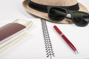 Passports, hat, camera ,glasses and pen on a paper floor ready to travel photo