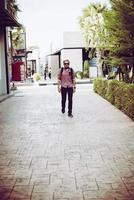 Portrait of a handsome hipster man in jeans and sunglasses walking photo