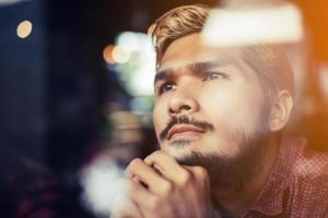 Pensive young hipster man sitting in a coffee shop thinking photo