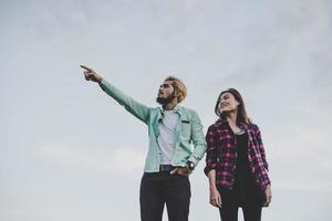 Loving hipster couple standing against clear sky