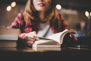 Adolescente hipster sentado y disfrutando de un libro en un café foto