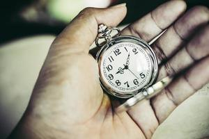 Close-up of a man's hand with a vintage pocket watch