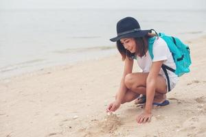 Young woman with a backpack sitting on the beach