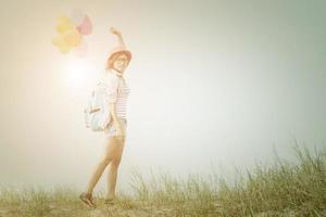 Teenage girl holding colorful balloons photo