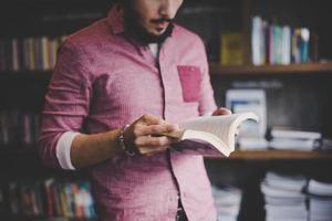 Hombre joven inconformista leyendo un libro en una biblioteca