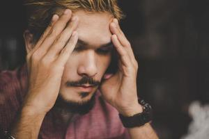 Young hipster man hand at a cafe with his hands on his head photo