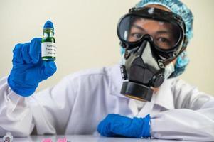 un científico que usa máscara y guantes lleva viales con vacunas para protegerse contra el covid-19 foto