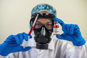 científico con máscaras protectoras y guantes sosteniendo una jeringa con una vacuna para prevenir la covid-19