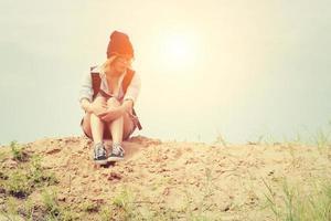 joven inconformista mujer sentada en la arena y llevar mochila sintiéndose tan triste