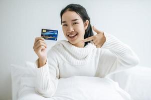 Mujer joven con una tarjeta de crédito sonriendo en la cama foto
