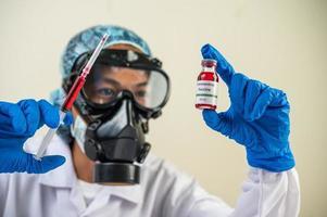 científico con máscaras protectoras y guantes sosteniendo una jeringa con una vacuna para prevenir la covid-19 foto