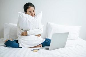 Young woman sitting on her bed and hugging pillow photo