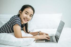 A woman wearing a striped shirt playing on her laptop on her bed