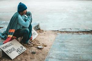 A man sits begging with homeless please help message photo