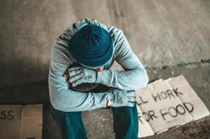 Beggars sitting under the overpass with help signs photo