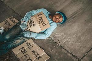 Beggar under the bridge with a cup of instant noodles and a help sign photo