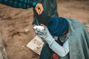 Beggar wrapped in cloth in the street accepting money photo
