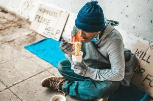 Homeless man wrapped in cloth and eating noodles