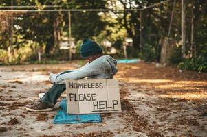 Beggar sitting on the street with homeless messages please help photo