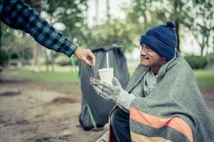 Mendigo envuelto en tela en la calle aceptando dinero foto