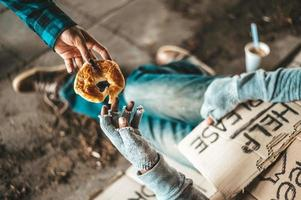 Beggar under the bridge with cardboard help signs accepting bread