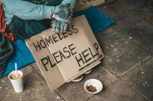 Man sits beside the street with a homeless message