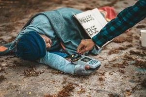 mendigo con una máquina de tarjetas de crédito