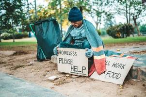 A man sitting with homeless please help message photo